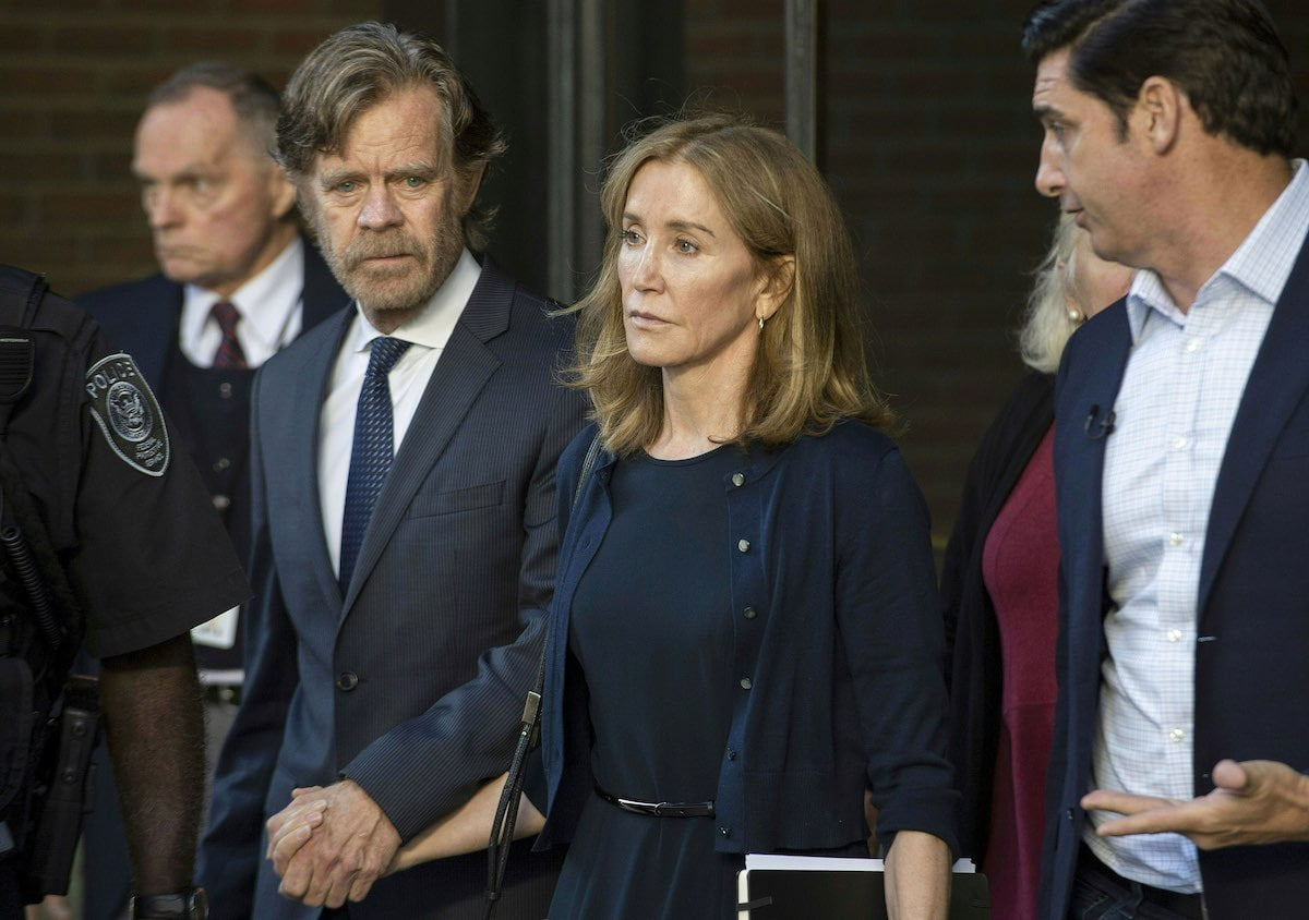 Felicity Huffman in a dark dress and cardigan walks hand in hand with William H. Macy in a suit at the courthouse