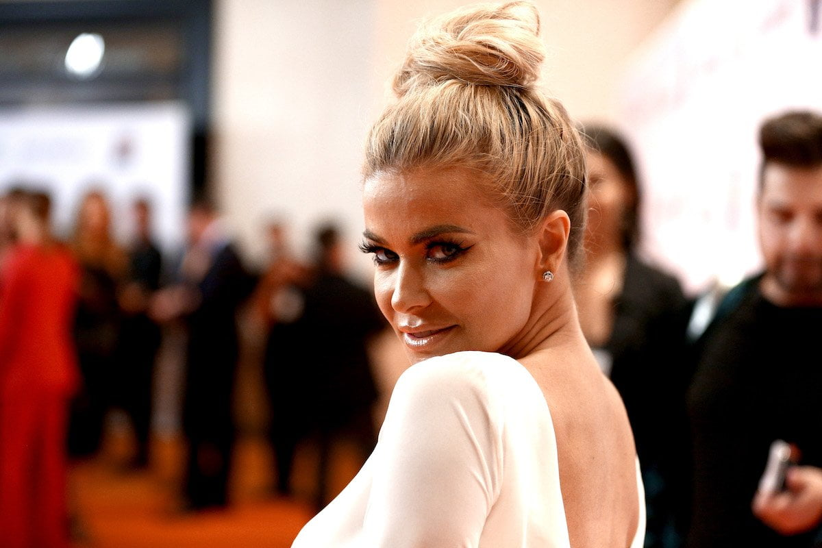 Carmen Electra smiles over her shoulder with her hair up and in a white dress