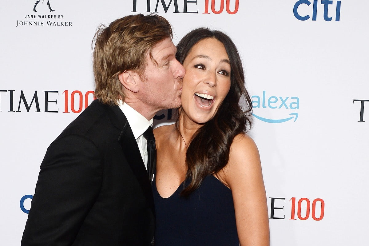 Chip Gaines in a black suit kisses the cheek of Joanna Gaines in a dark navy dress