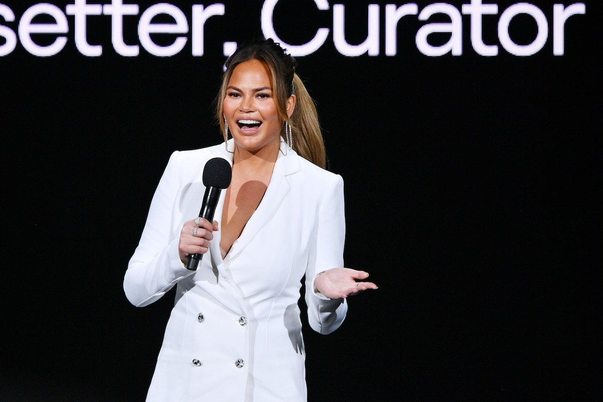 Chrissy Teigen laughs holding a mic dressed in a white pantsuit against a black background