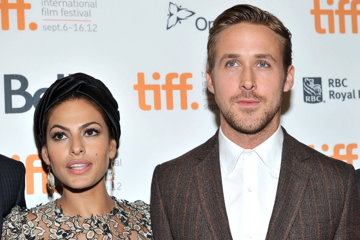 Eva Mendes in a silvery dress smiles next to Ryan Gosling in a brown suit jacket and white shirt