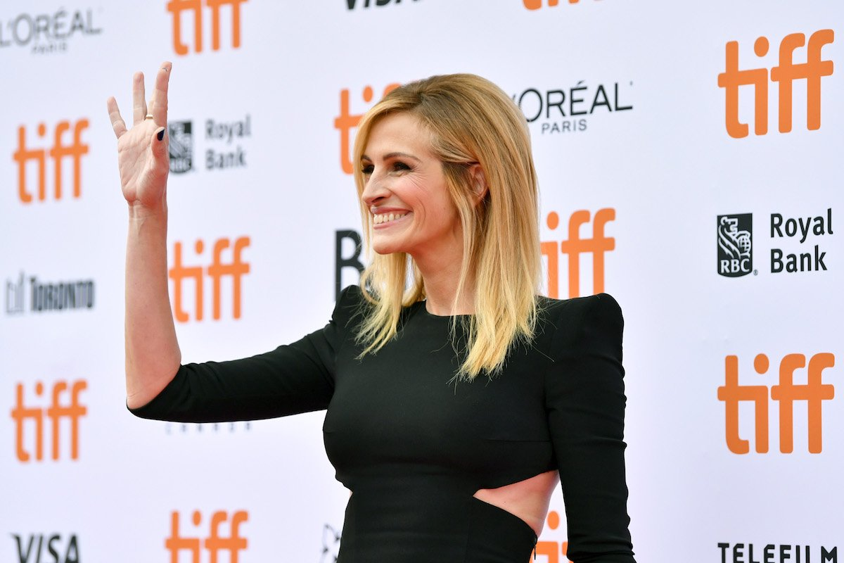 Julia Roberts waves and smiles in a black dress