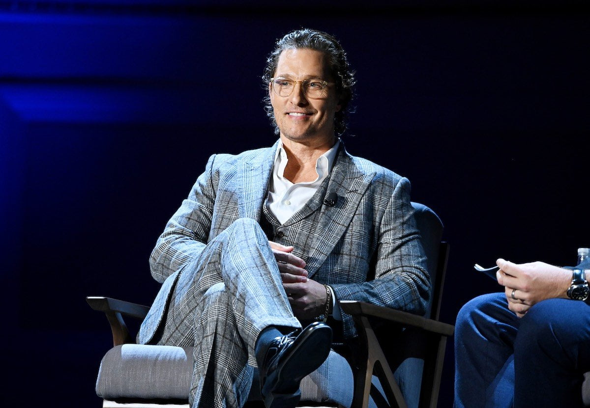 Matthew McConaughey smiles dressed in a grey suit sitting on a grey chair