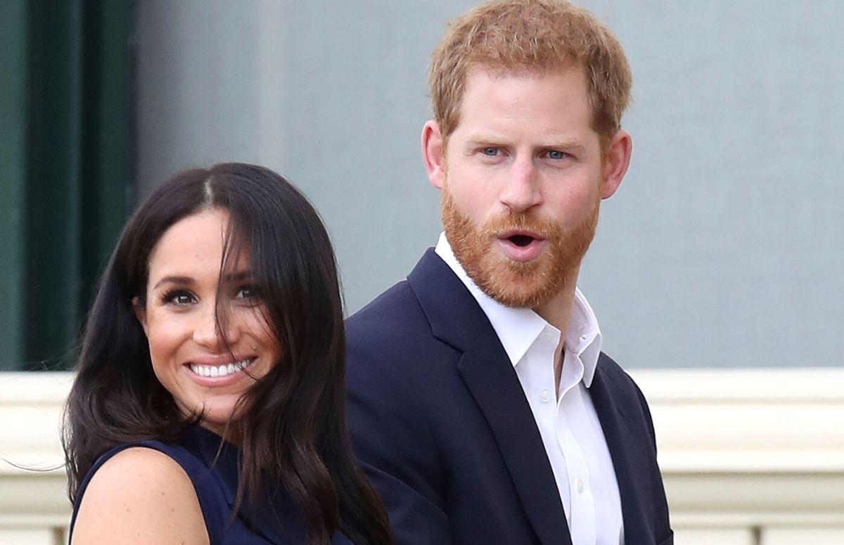 Meghan Markle wearing a black dress walking with Prince Harry, who's wearing a dark blue blazer, in Australia