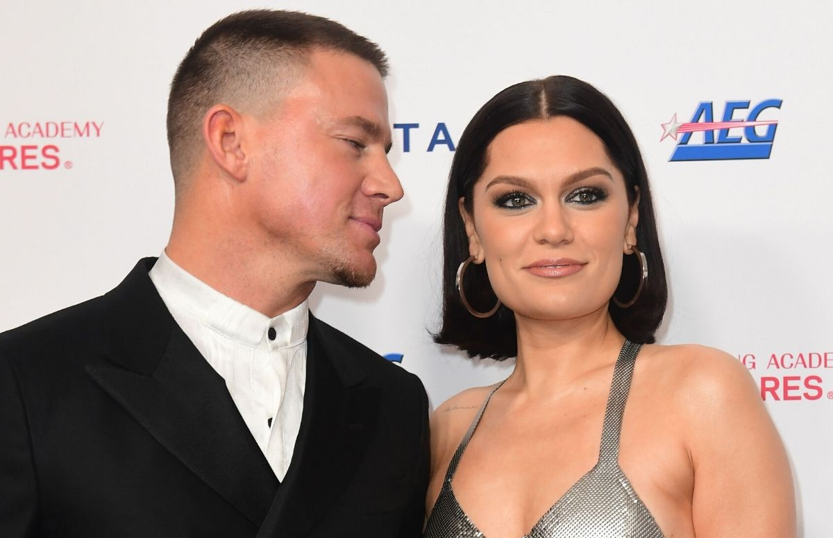 Channing Tatum wearing a black suit standing with Jessie J, who's wearing a silver dress, on the red carpet