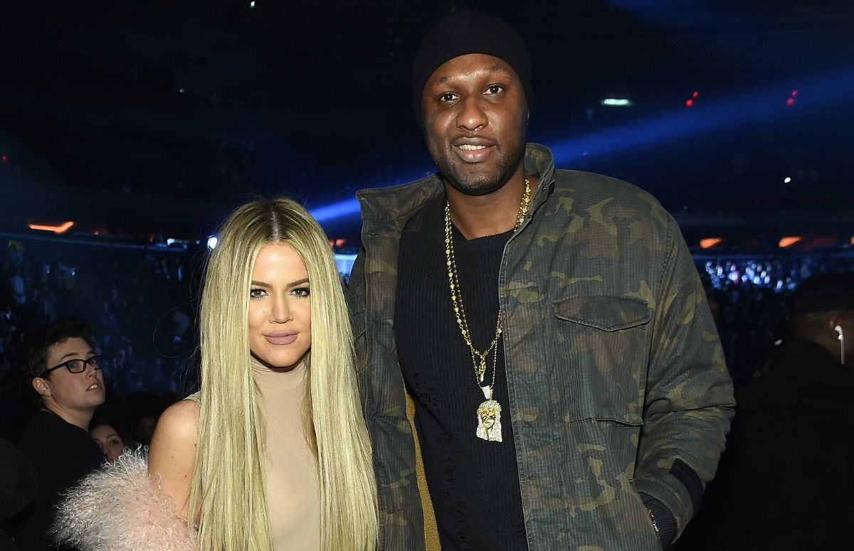 Khloe Kardashian in a beige top standing with Lamar Odom, who's wearing a camouflage jacket, at the Kanye West Yeezy Season 3 show