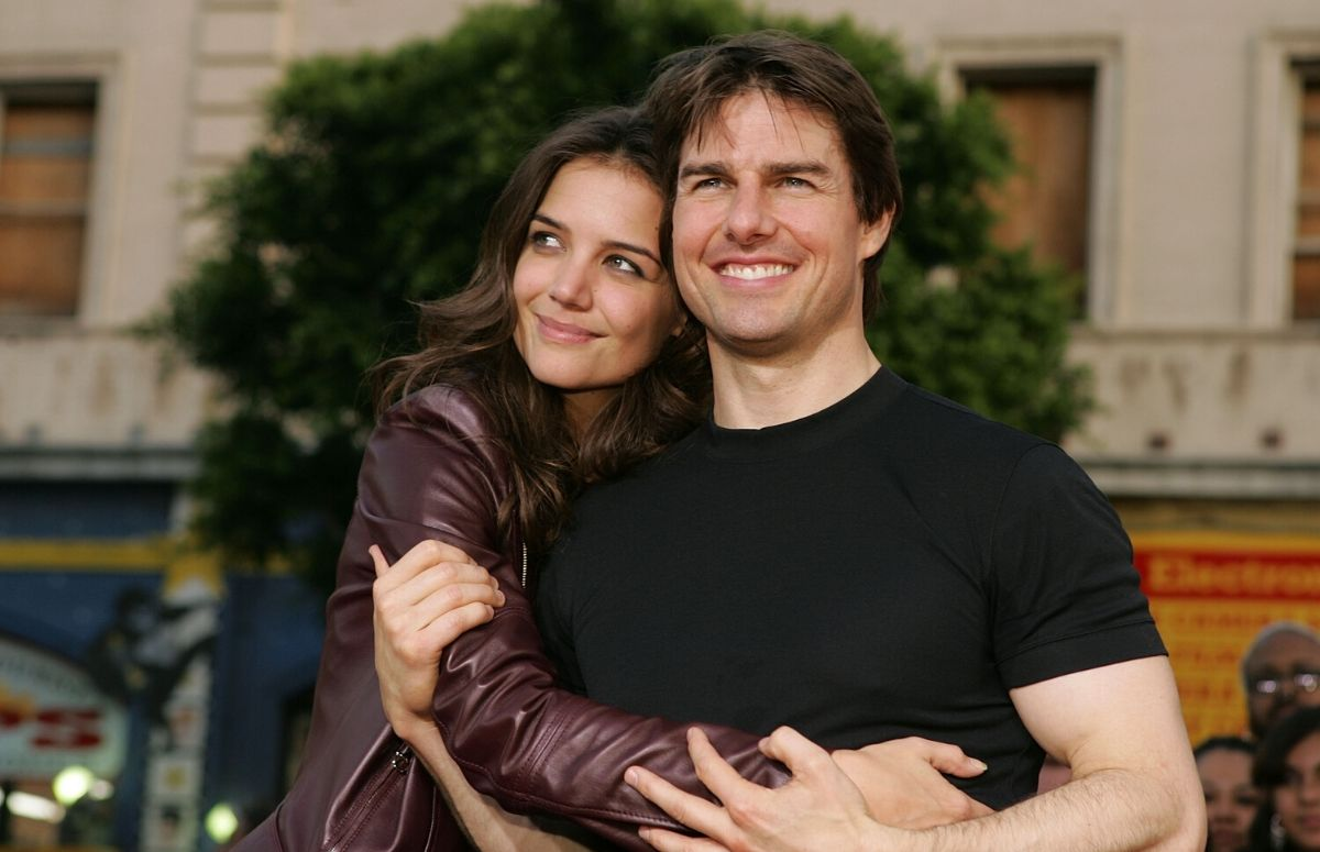 Katie Holmes wearing a brown jacket cuddling with Tom Cruise, who's wearing a black t-shirt at a fan screening.
