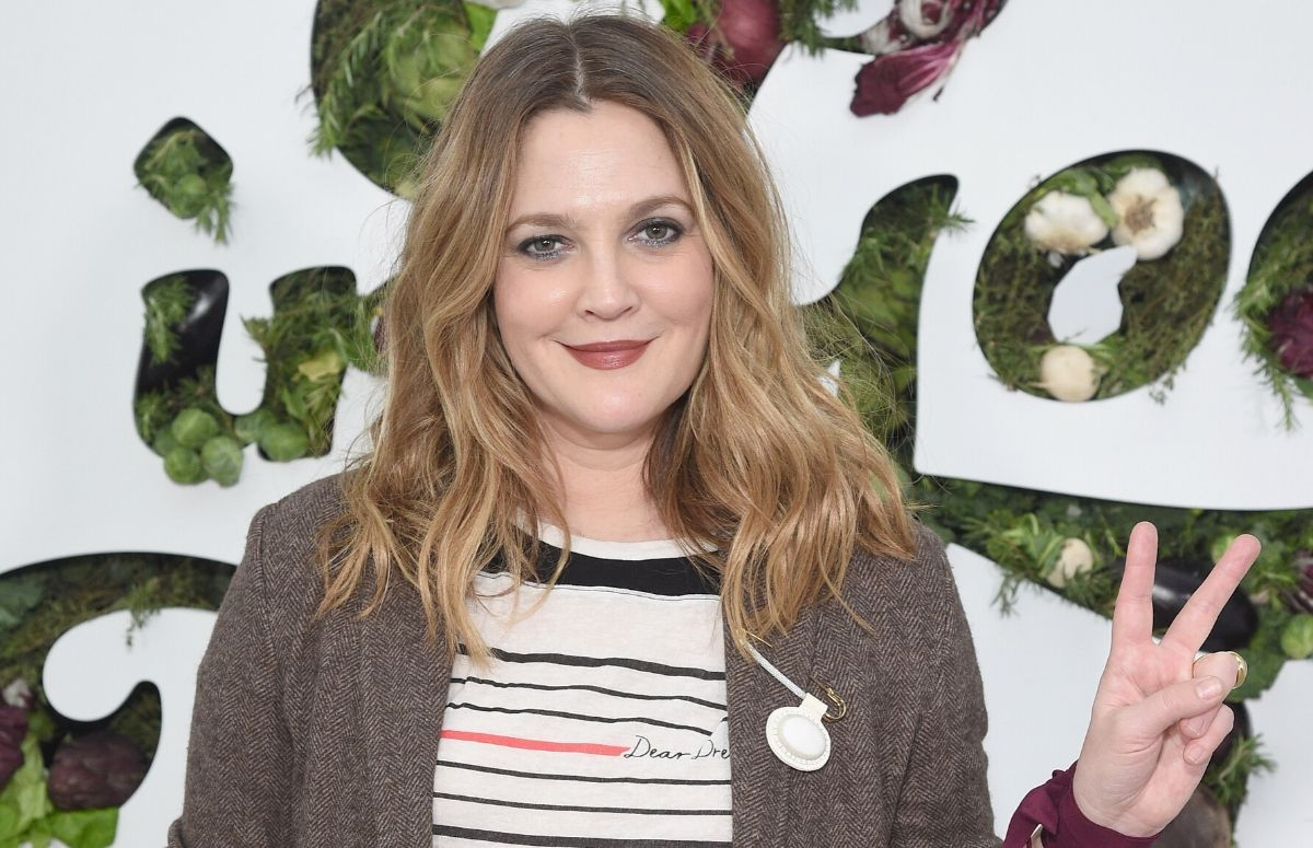Drew Barrymore wearing a brown sweater and a stripped top on the red carpet