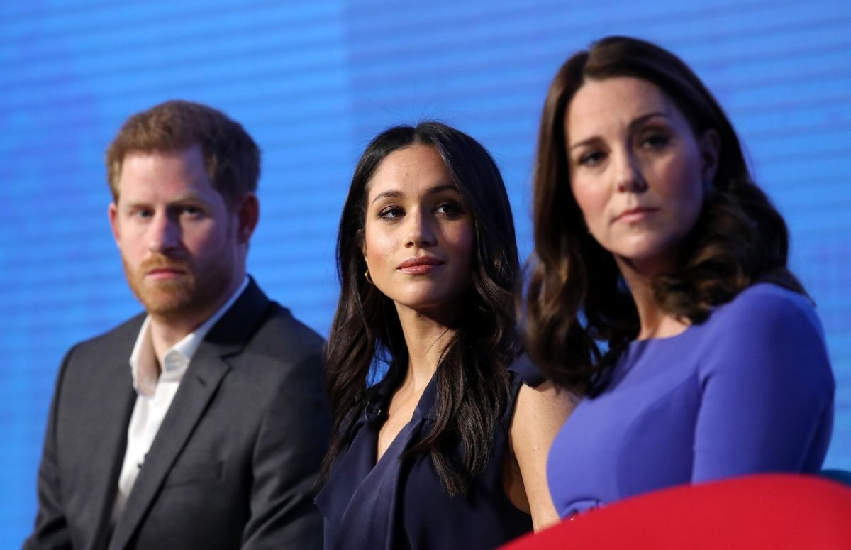 Prince Harry wearing a gray suit, Meghan Markle wearing a dark blue dress, and Kate Middleton wearing a purple gown sitting onstage First Annual Royal Foundation Forum