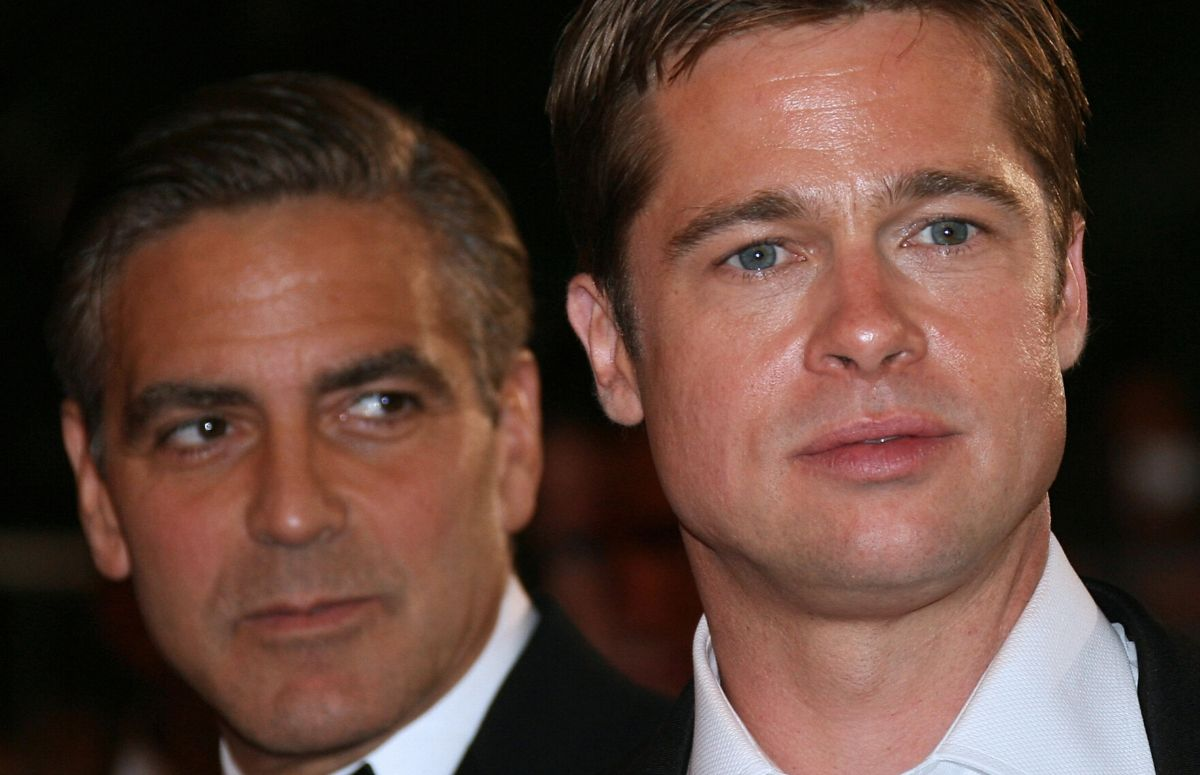 George Clooney wearing a black tux standing with Brad Pitt, who's in a black suit, on the red carpet