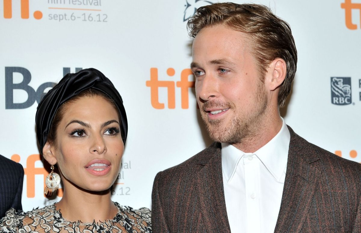 Eva Mendes in a black lace dress standing with Ryan Gosling, who's wearing a brown suit, on the red carpet