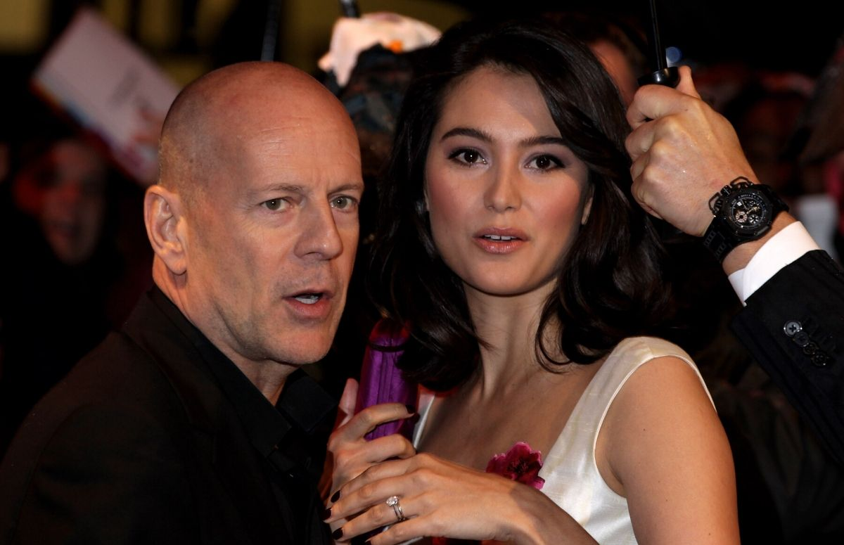 Bruce Willis wearing a black suit standing with Emma Hemming, who's wearing a white dress, on the red carpet