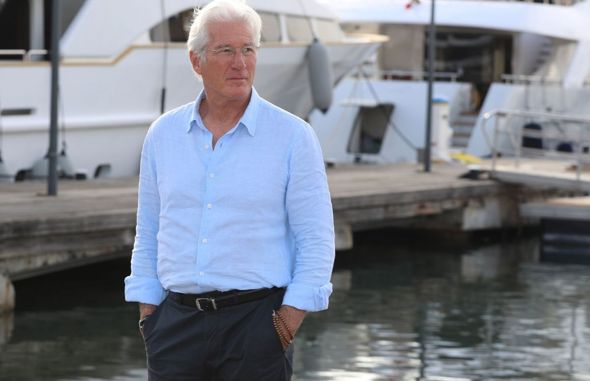 Richard Gere wearing a light blue shirt and gray pants at a photocall in France