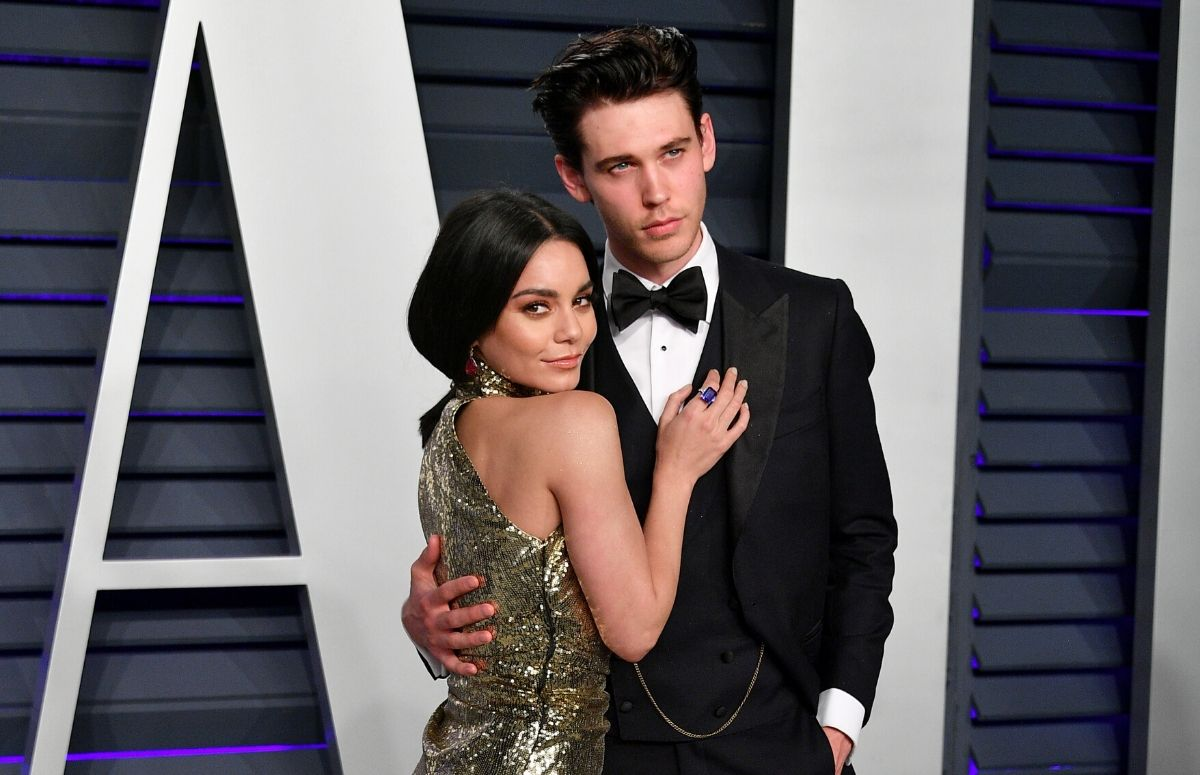 Vanessa Hudgens wearing a gold dress standing with Austin Butler, who's wearing a black tux, on the red carpet