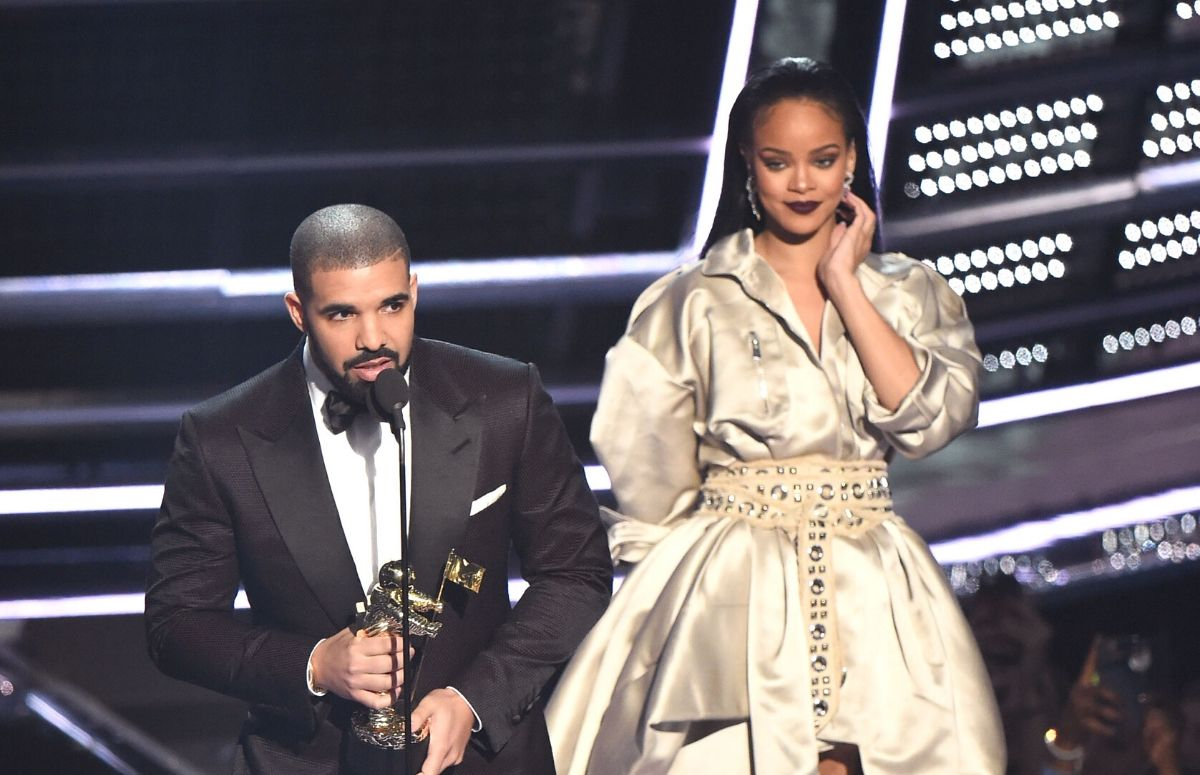 Drake wearing a black tux on stage at the 2016 VMAs with Rihanna, who's wearing an off-white dress.