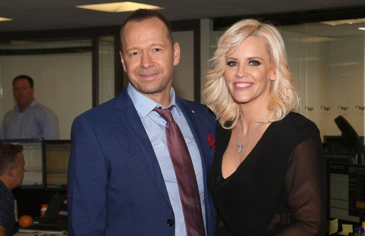 Donnie Wahlberg wearing a blue suit standing with Jenny McCarthy, who's wearing a black dress, at a charity event