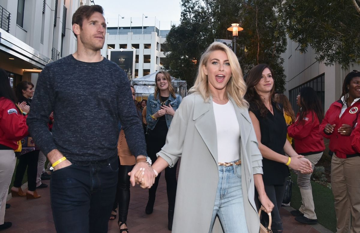 Julianne Hough wearing blue jeans, a white shirt, and a gray coat walking with Brooks Laich, who's wearing a blue sweater and dark blue jeans at an LA spring break event