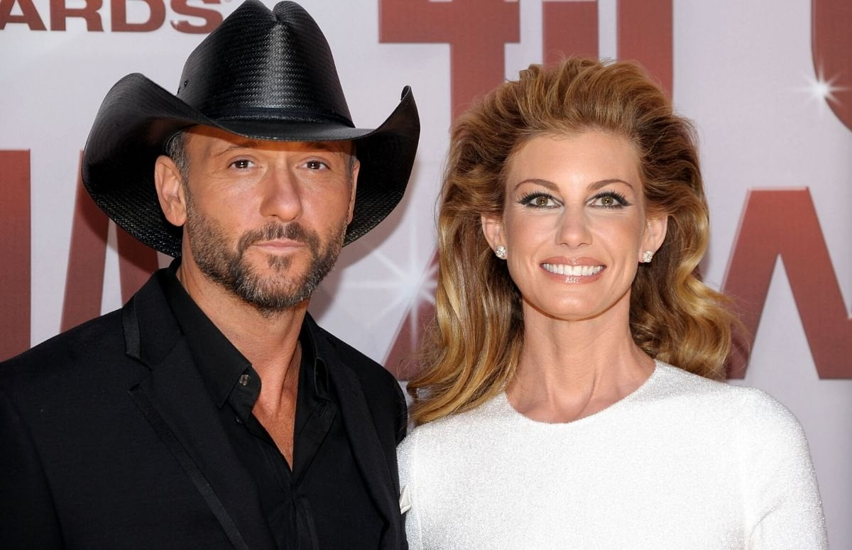 Tim McGraw wearing a black suit and black cowboy hat standing with Faith Hill, who's wearing a white dress, on the red carpet