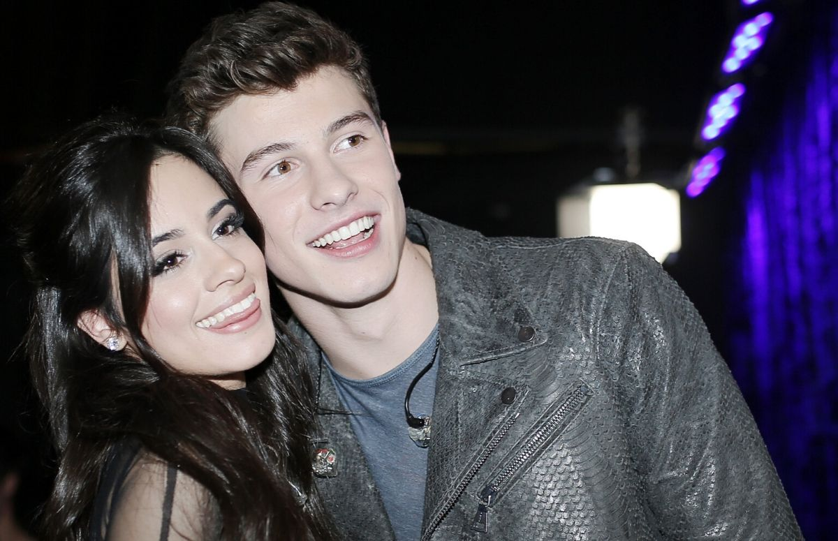 Camila Cabello wearing a black dress standing with Shawn Mendes, who's wearing a black jacket, backstage at the People's Choice Awards