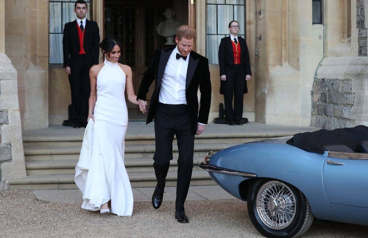 Meghan Markle, wearing a white gown, walking with Prince Harry, who's wearing a black tux, on their wedding day