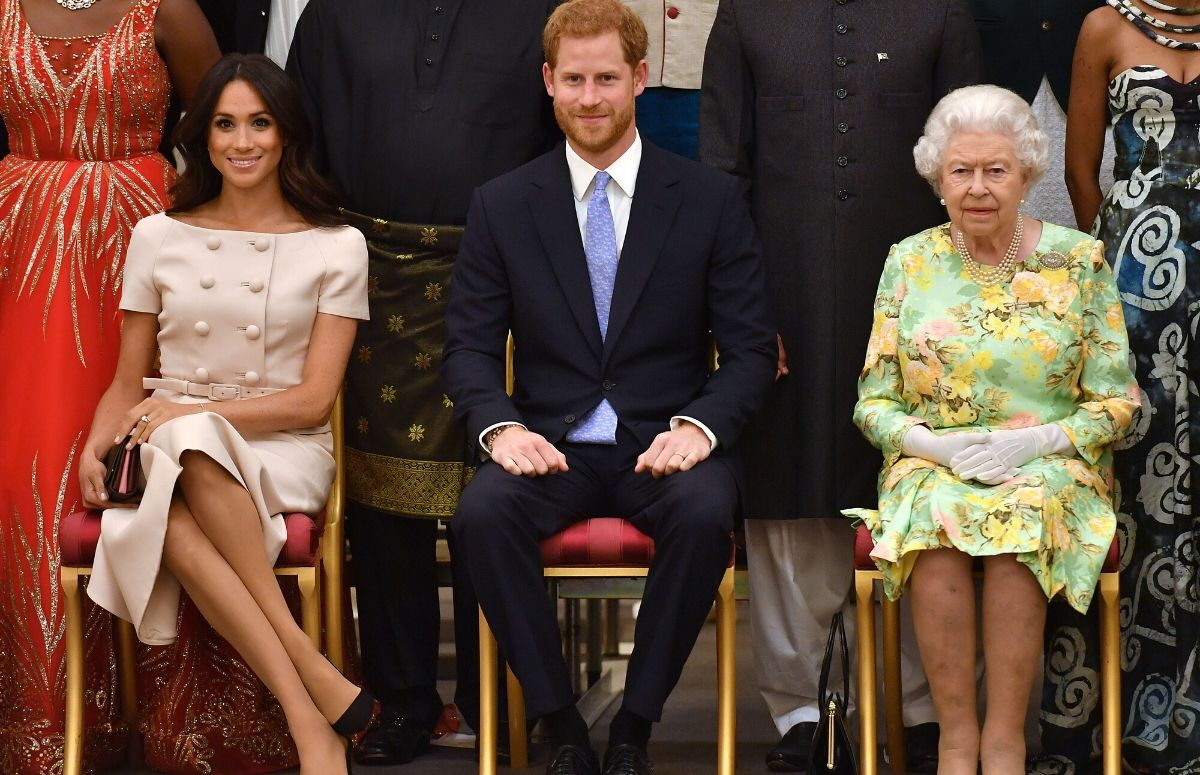 Meghan Markle in a peach dress sitting with Prince Harry, who's in a black suit, and Queen Elizabeth II, who's wearing a green dress
