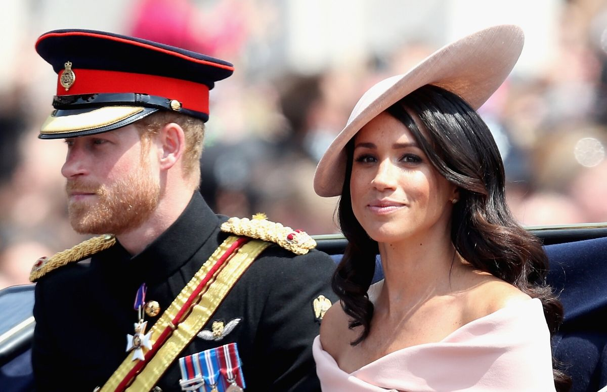 Prince Harry wearing his military uniform sitting with Meghan Markle, who's wearing a pink hat and dress, in an open carriage as part of Trooping the Color