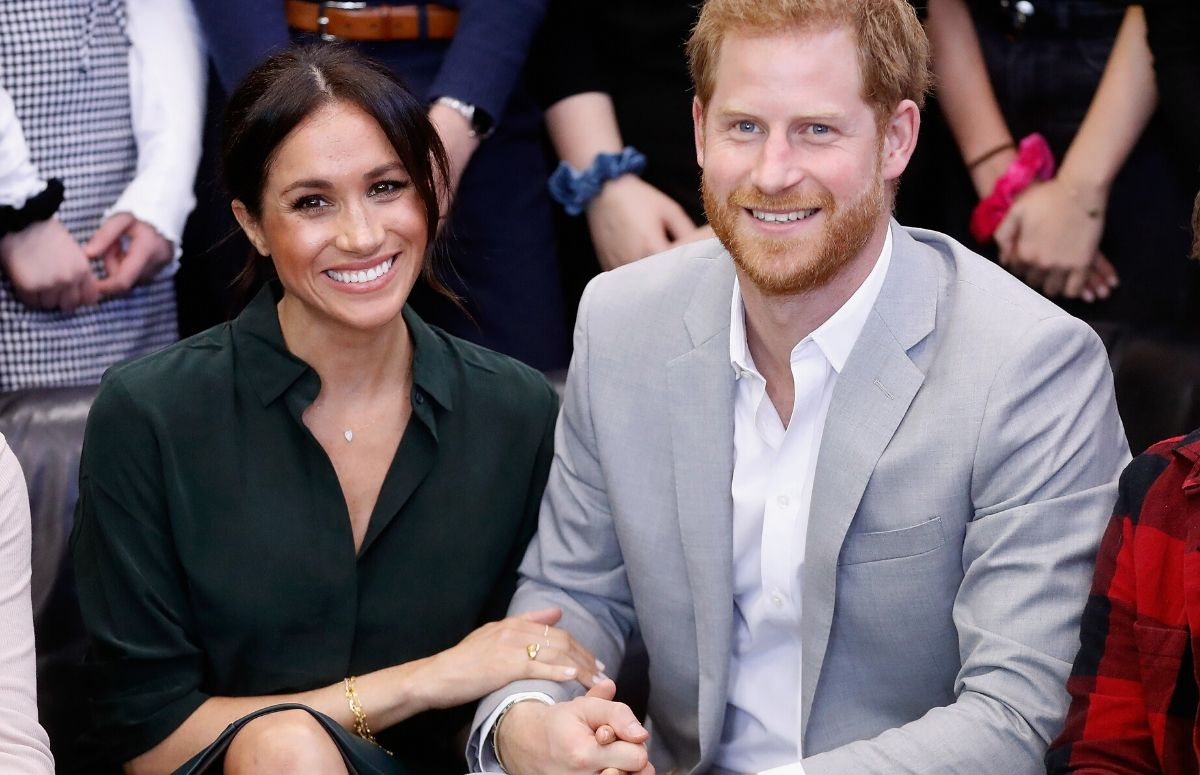 Meghan Markle, wearing a green blouse, sitting with Prince Harry, who's wearing a gray suit at a public event
