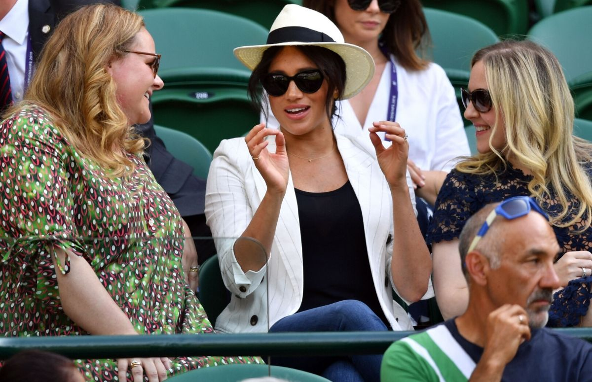 Meghan Markle, wearing a black t shirt, white blazer, and jeans, sitting with two friends at Wimbledon