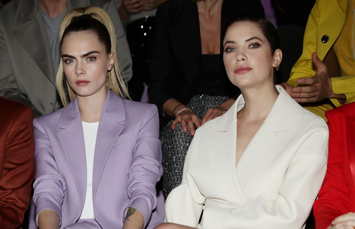 Cara Delevingne wearing a purple suit sitting front row with Ashley Benson, who's wearing a white suit, at the Milan Fashion Show