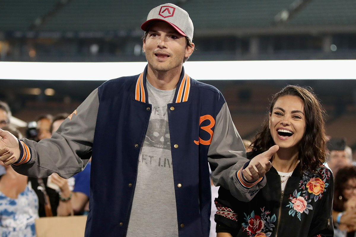 Ashton Kutcher looking bemused as Mila Kunis laughs at something next to him.