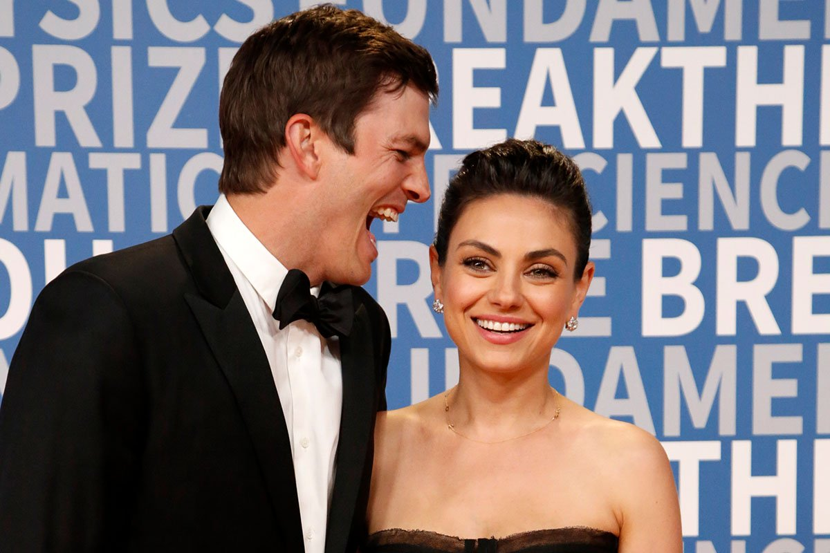 Ashton Kutcher laughing in Mila Kunis' ear at a red carpet event.