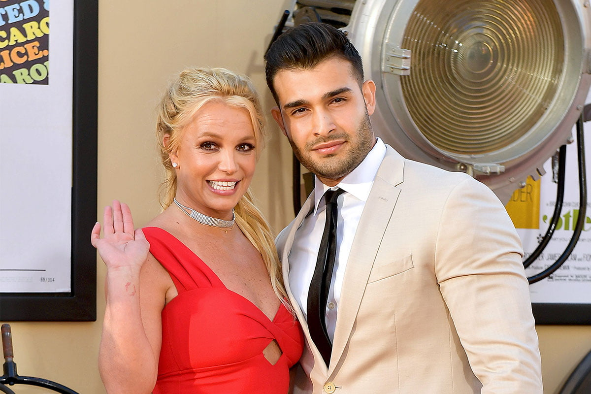 Britney Spears waving for the camera in a red dress with Sam Asghari next to her with his arm around her.