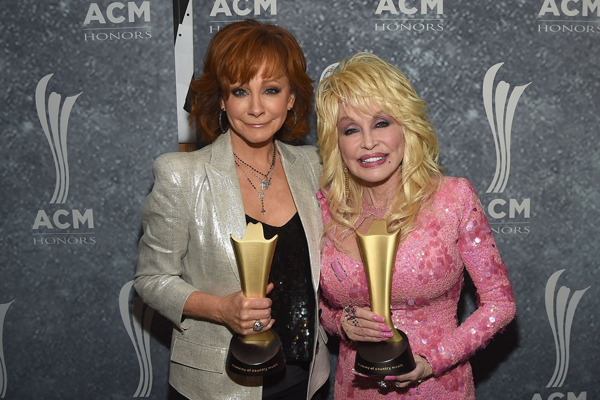 Reba McEntire on the leftm Dolly Parton on the right, celebrating their CMA awards together.