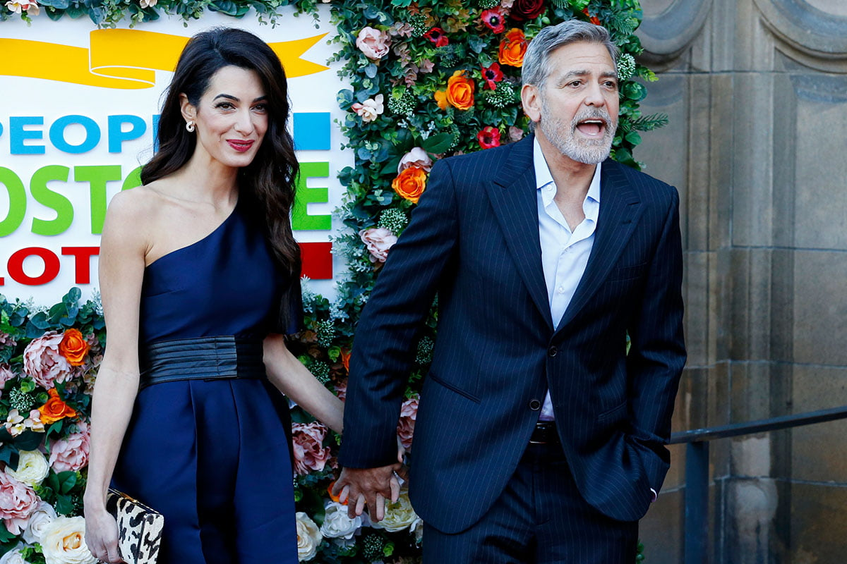 George and Amal Clooney holding hands at a charity event last year.