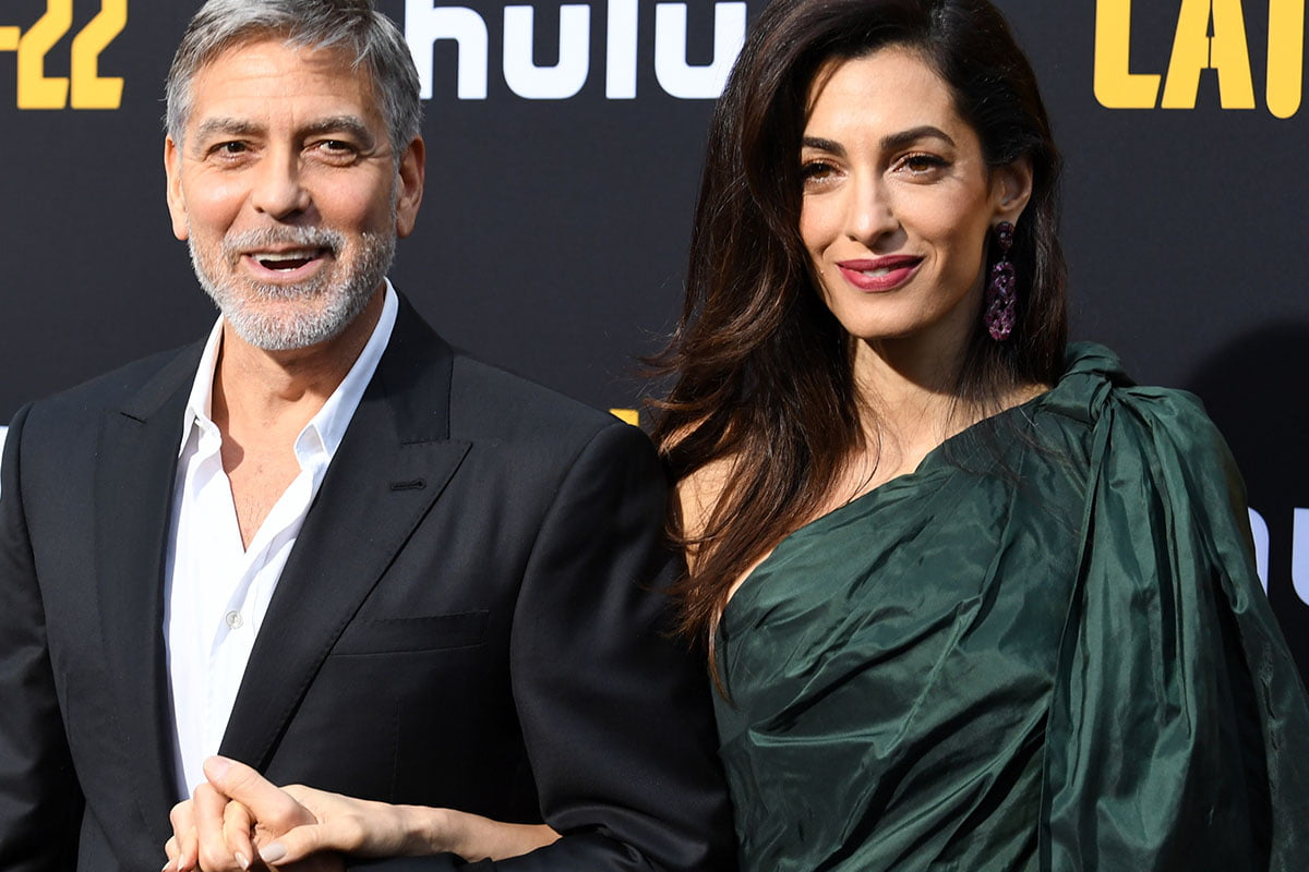 George Clooney and Amal Clooney holding hands at a movie premiere