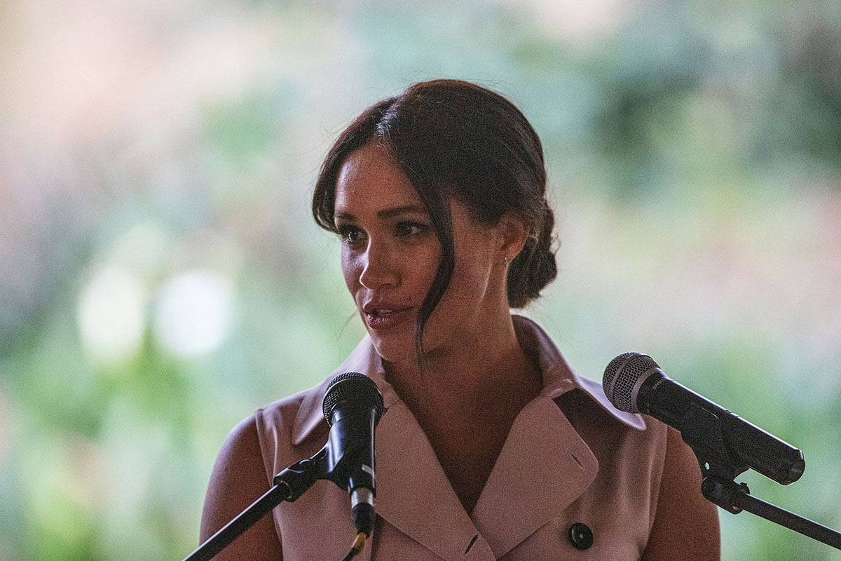 Meghan Markle standing in front of two microphones.