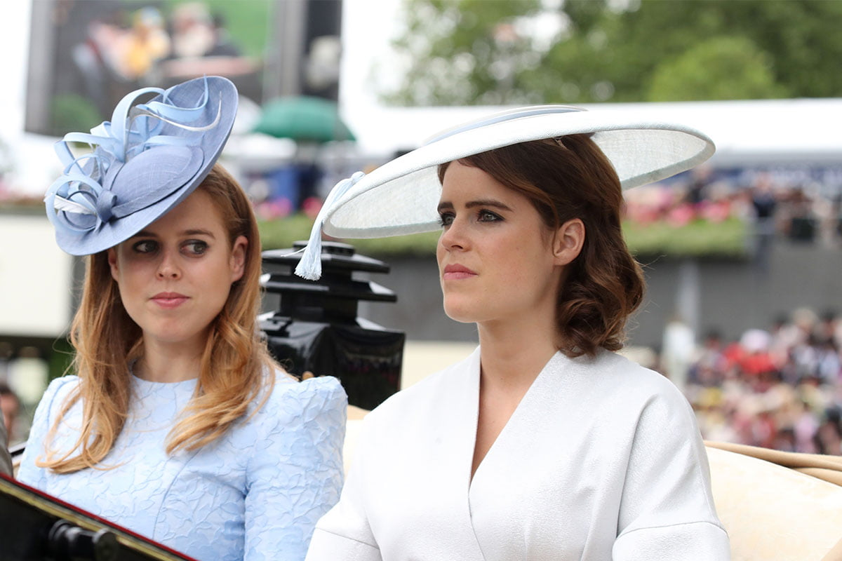 Princess Beatrice on the left and Princess Eugenie on the right, riding in a carriage with big hats on.