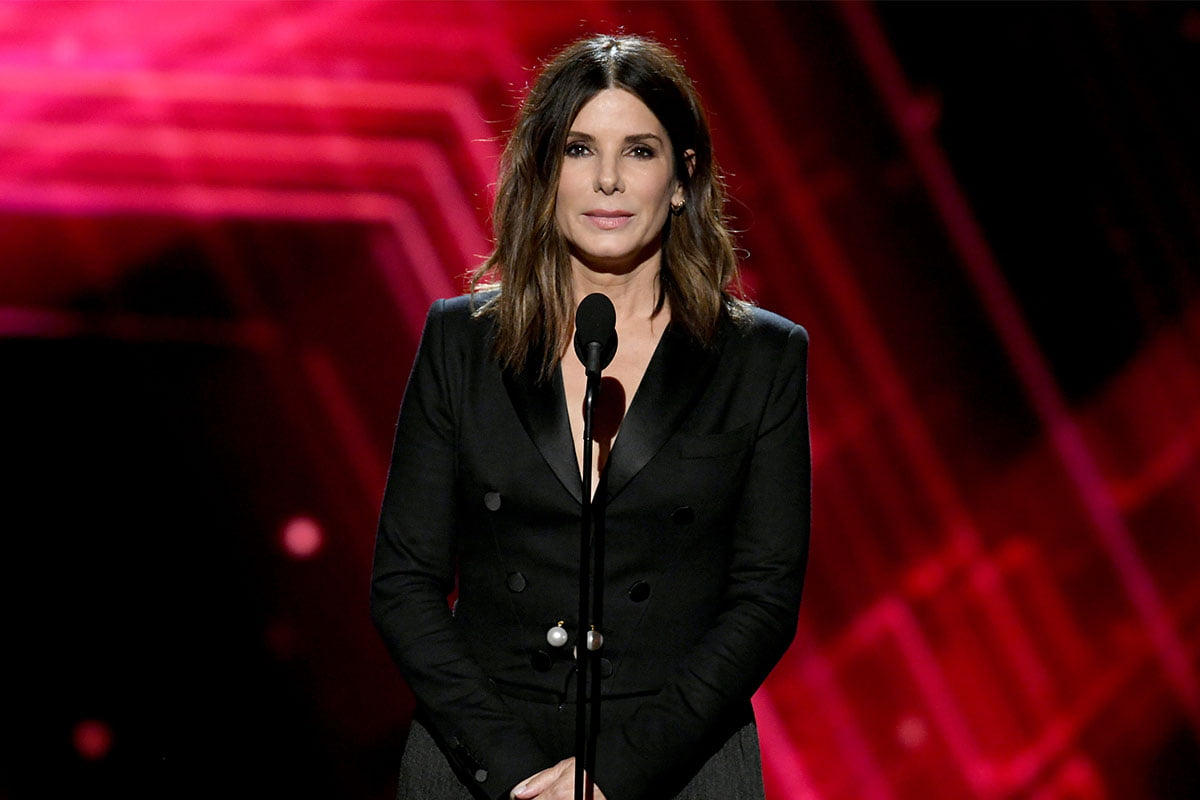 Sandra Bullock in all black standing at a microphone