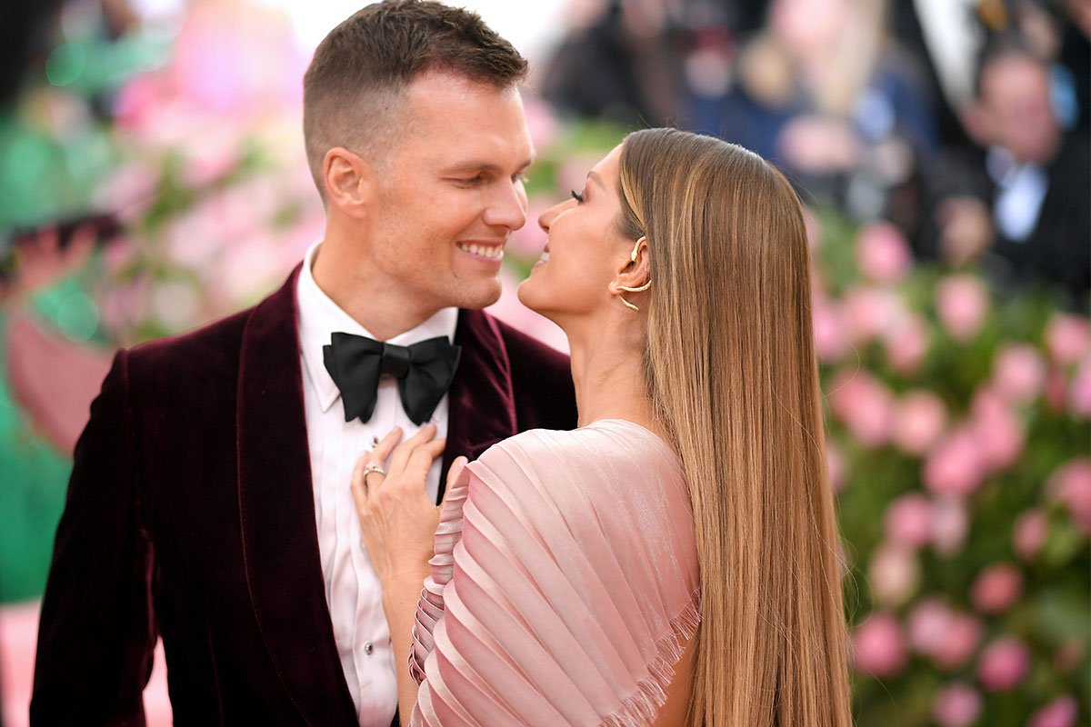 Tom Brady and Gisele Bündchen looking at each other and smiling.