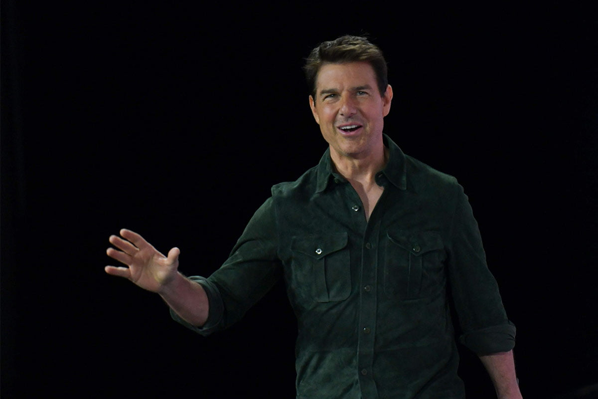 Tom Cruise waving in front of a dark background
