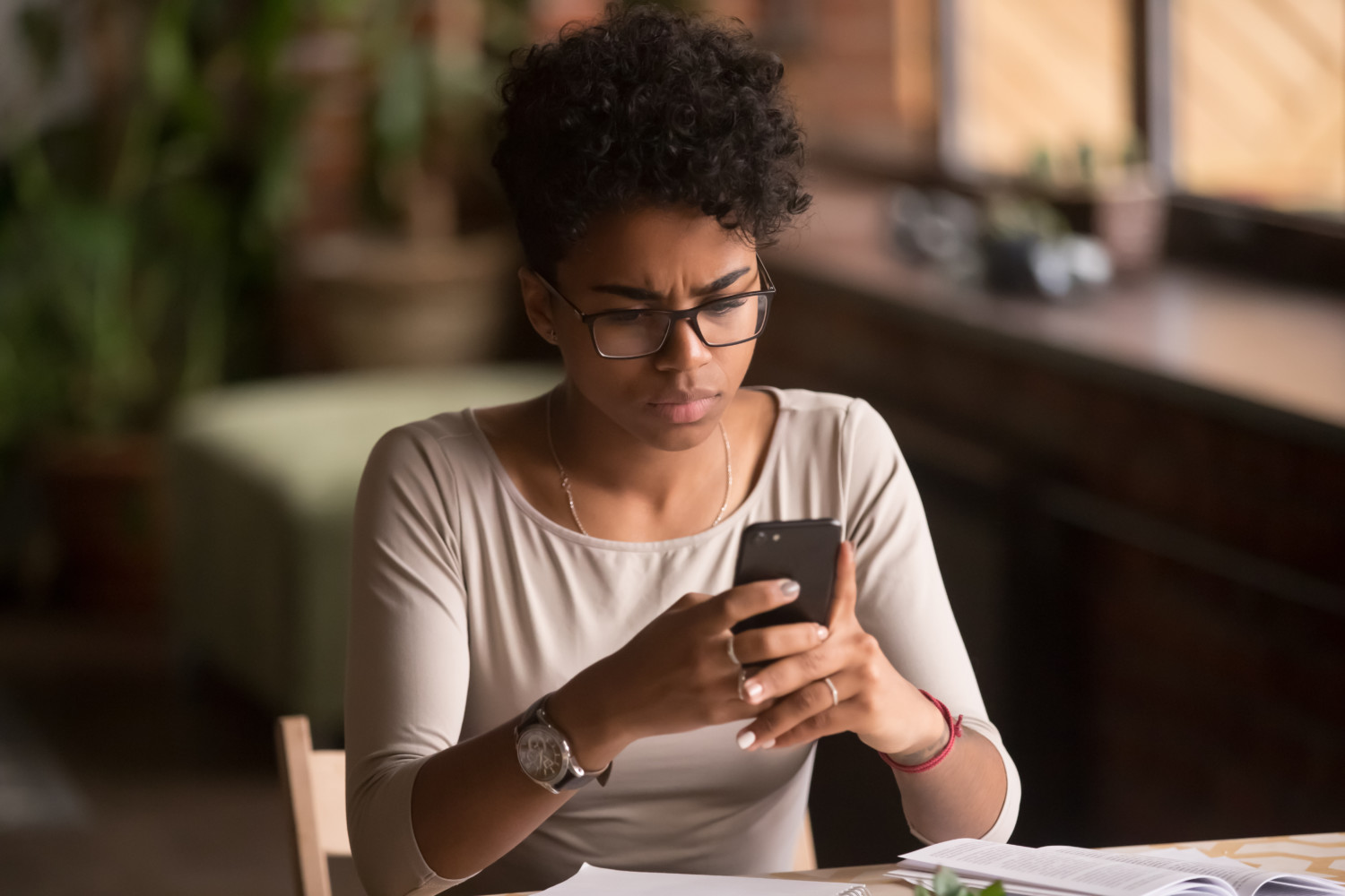 Confused woman looks at cell phone