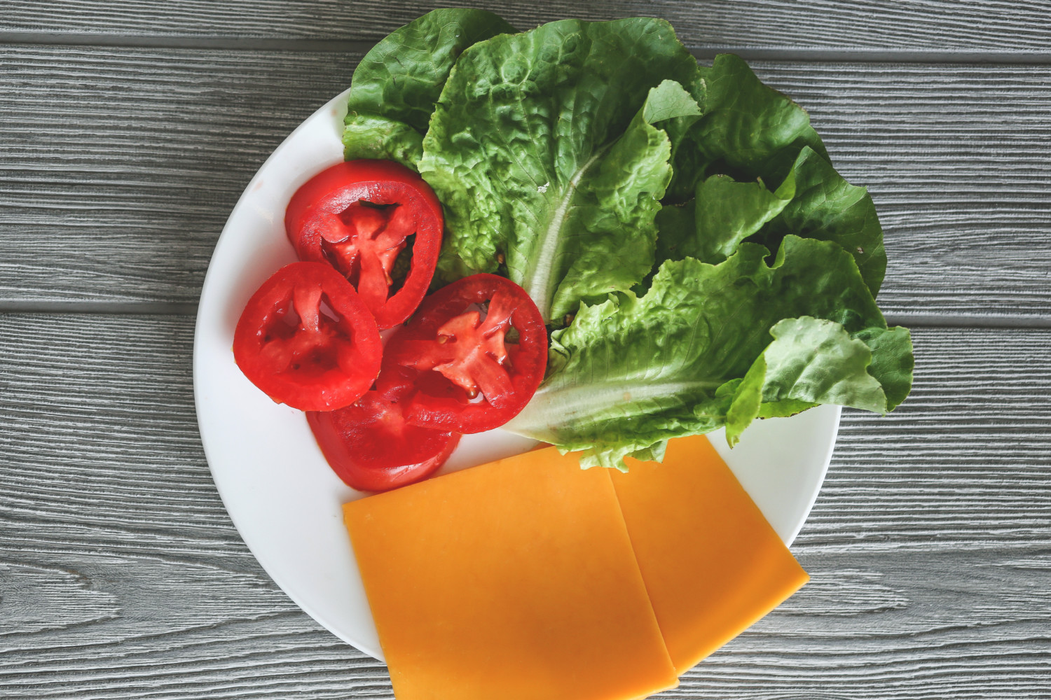 Lettuce, tomato and cheese burger toppings on white plate